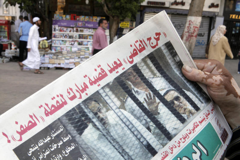 "An Egyptian reads a newspaper with a picture of former Egyptian President Hosni Mubarak waving behind bars during a trial hearing, in Tahrir Square Cairo, Egypt, Sunday, April 14, 2013. The judge in Hosni Mubarak's retrial recused himself at the start of the first session on Saturday, citing a conflict of interest as the former Egyptian president appeared in court for the first time in 10 months grinning and waving to supporters. Arabic reads, ""The judge's recusal takes Mubarak's case to square one."" (AP Photo/ Amr Nabil)"