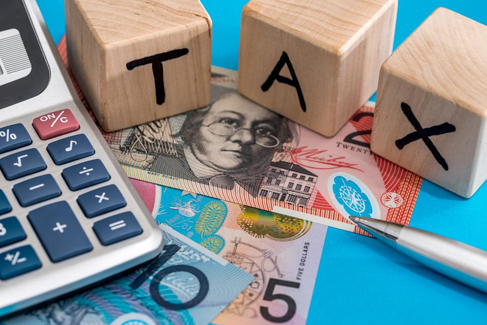 Wooden blocks spelling out tax with Australian bank notes, pen and calculator.
