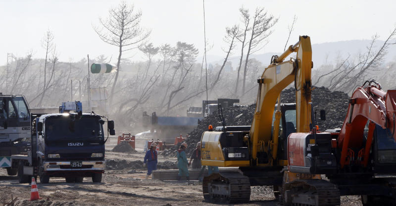 In this Oct. 9, 2012 photo, with a backdrop of leaning pine trees, part of windbreak forests severely damaged by the March 11, 2011 earthquake and tsunami, construction works continue near the Arahama Beach in Sendai, northeastern Japan. Japan's accounting of its budget for reconstruction from the disasters is crammed with spending on unrelated projects, while all along Japan's northeastern coast, dozens of communities remain uncertain of whether, when and how they will rebuild. (AP Photo/Koji Sasahara)
