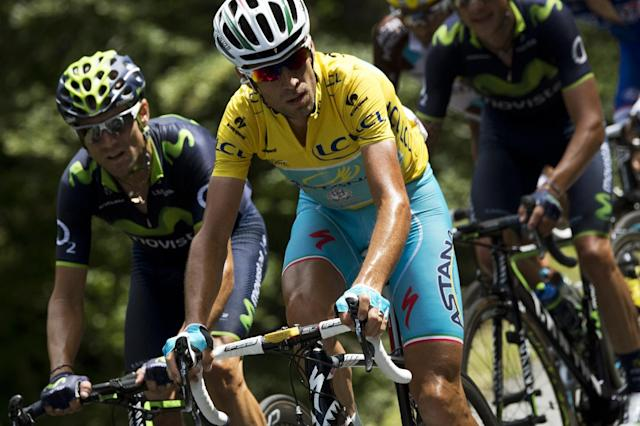 Italy's Vincenzo Nibali (C) wearing the overall leader's yellow jersey, rides in the pack next to Spain's Alejandro Valverde (L) during the 16th stage of the Tour de France between Carcassonne and Bagneres-de-Luchon, southwest France on July 22, 2014 (AFP Photo/Lionel Bonaventure)