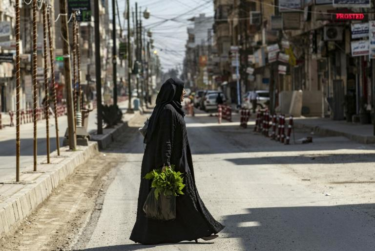 A woman carrying groceries crosses a deserted street in northeast Syria's Kurdish-majority city of Qamishli