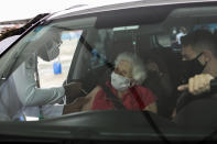 An elderly woman receives a dose of the China's Sinovac Biotech COVID-19 vaccine at a drive-thru vaccination site in the Sambadrome, in Rio de Janeiro, Brazil, Saturday, Feb. 6, 2021. In a normal year, Rio's Sambadrome would be preparing for its great moment of the year: the world's most famous Carnival parade. But a week before what should be the start of Carnival, the pandemic has replaced pageantry. (AP Photo/Bruna Prado)