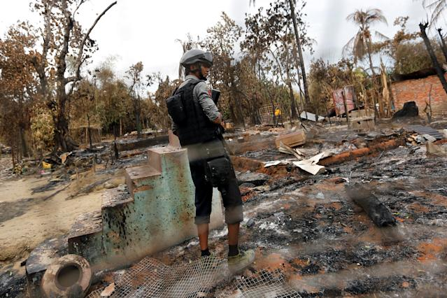 <p>A police officer stands in a house that was burnt down during the days of violence in Maungdaw, Myanmar, Aug. 30, 2017. (Photo: Soe Zeya Tun/Reuters) </p>