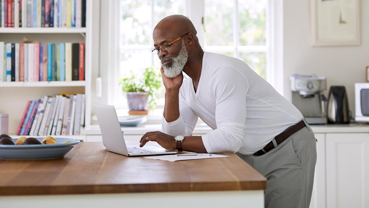 Shot of a mature man using a laptop while working out his retirement plan at home..