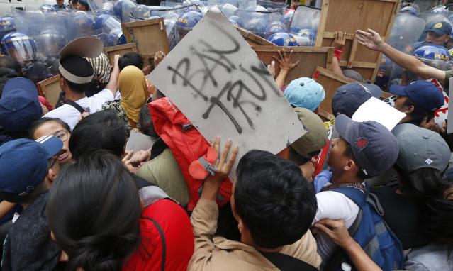 <p>Protesters scuffle with riot police as the former try to force their closer to U.S. Embassy in Manila to protest this weekend's visit of U.S. President Donald Trump Friday, Nov. 10, 2017 in Manila, Philippines. (Photo: Bullit Marquez/AP) </p>