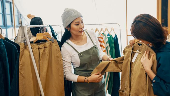Retail shop clerk helping a mid adult woman customer shop for clothing in a boutique in Japan.