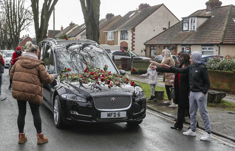 Members of the public place red roses on the hearse of Olly Stephens in February (Steve Parsons/PA) (PA Archive)