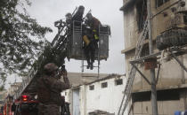 Rescue workers retrieve a body from a burnt chemical factory, in Karachi, Pakistan, Friday, Aug. 27, 2021. A massive fire broke out at a chemical factory in Pakistan's southern port city of Karachi on Friday, killing some workers and injuring several others, police and a government spokesman said. (AP Photo/Ikram Suri)