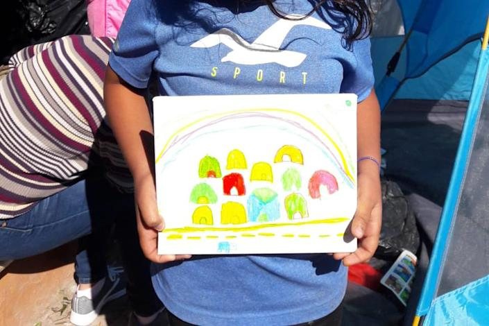 A young girl holds up her drawing of the Matamoros tent encampment where she lives. | Courtesy of Belinda Arriaga