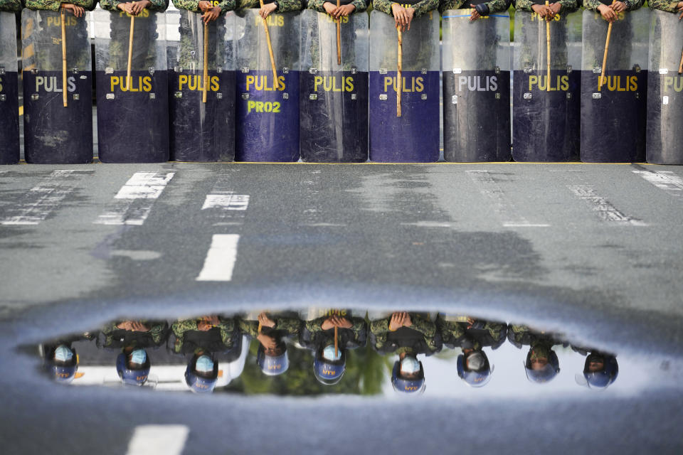 Police are reflected in a puddle of water as they secure the area where politicians will file their certificate of candidacy before the Commission on Elections on Friday, Oct. 1, 2021 in Manila, Philippines. Friday marks the start of a weeklong registration period for candidates seeking to lead the Southeast Asian nation that has been hit hard by the pandemic and deep political conflicts. (AP Photo/Aaron Favila)