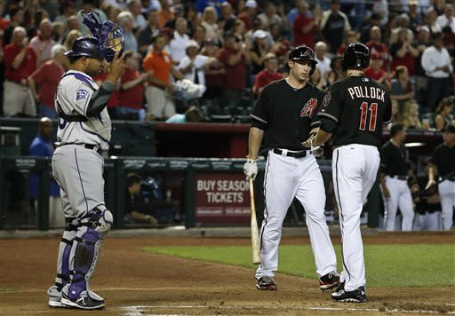 Arizona Diamondbacks' A.J. Pollock (11) celebrates his home run with teammate Paul Goldschmidt as Colorado Rockies' Wilin Rosario, left, looks on in the first inning during a baseball game, on Saturday, April 27, 2013, in Phoenix. AP Photo/Ross D. Franklin)