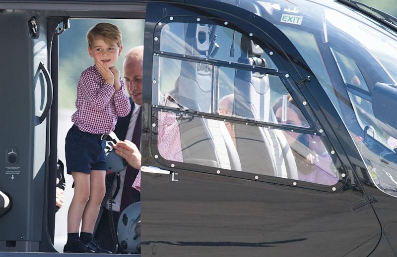 Prince George boards the helicopter in a button-down shirt and shorts.