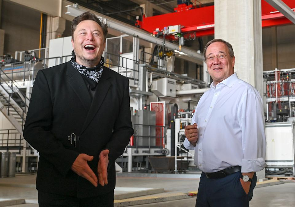 Tesla CEO Elon Musk and Armin Laschet, CDU Federal Chairman and Prime Minister of North Rhine-Westphalia, talk during a tour of the plant of the future foundry of the Tesla Gigafactory on August 13, 2021 in Grünheide near Berlin, Germany. (Credit: Patrick Pleul/Getty Images)