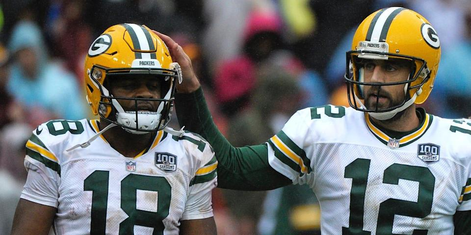 Aaron Rodgers pats the helmet of Randall Cobb during a 2018 game.