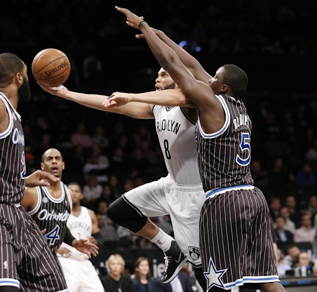 Brooklyn Nets guard Deron Williams (8) goes up for a layup with Orlando Magic guard Victor Oladipo (5) defending in the first half of their NBA basketball game at the Barclays Center, Tuesday, Jan. 21, 2014 in New York. (AP Photo/Kathy Willens)