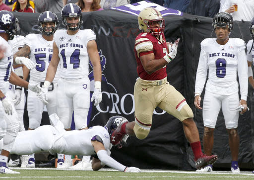 FILE - In this Sept. 8, 2018, file photo, Boston College running back AJ Dillon (2) rushes down the sideline past Holy Cross players during the first half of an NCAA college football game in Boston. (AP Photo/Mary Schwalm, File)