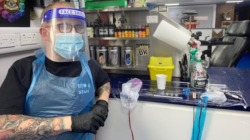 Tattoo artist Adam Grant wears a face mask, visor and disposable gloves and apron.