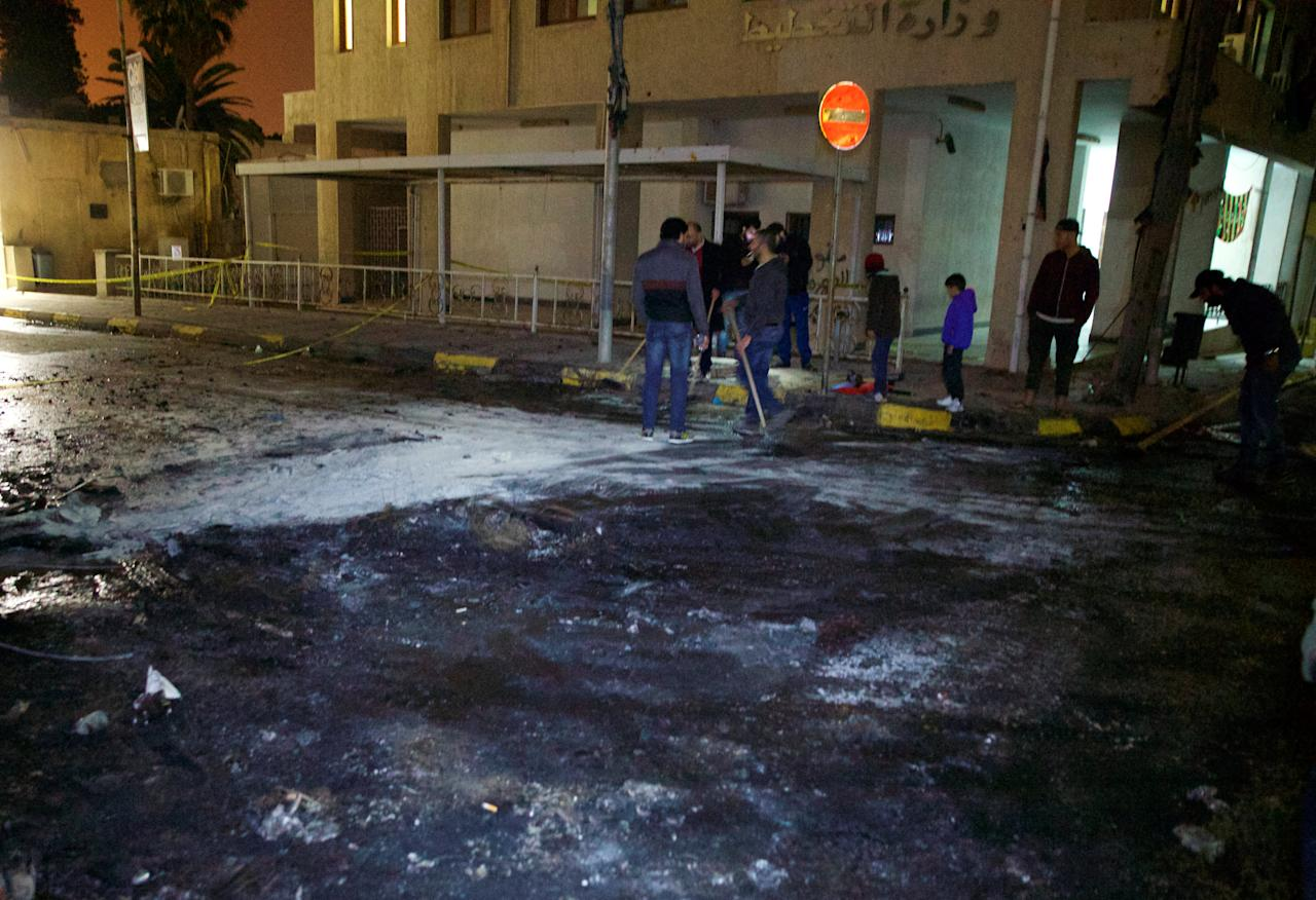 People clean the scene where a car bomb exploded late on Saturday close to the recently re-opened Italian embassy in Tripoli, Libya January 21, 2017. Picture taken January 21, 2017. REUTERS/Stringer EDITORIAL USE ONLY. NO RESALES. NO ARCHIVE.
