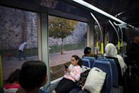 FILE PHOTO: A girl uses a mobile phone as she rides a light rail tram in Jerusalem November 11, 2014. REUTERS/Ronen Zvulun/File Photo