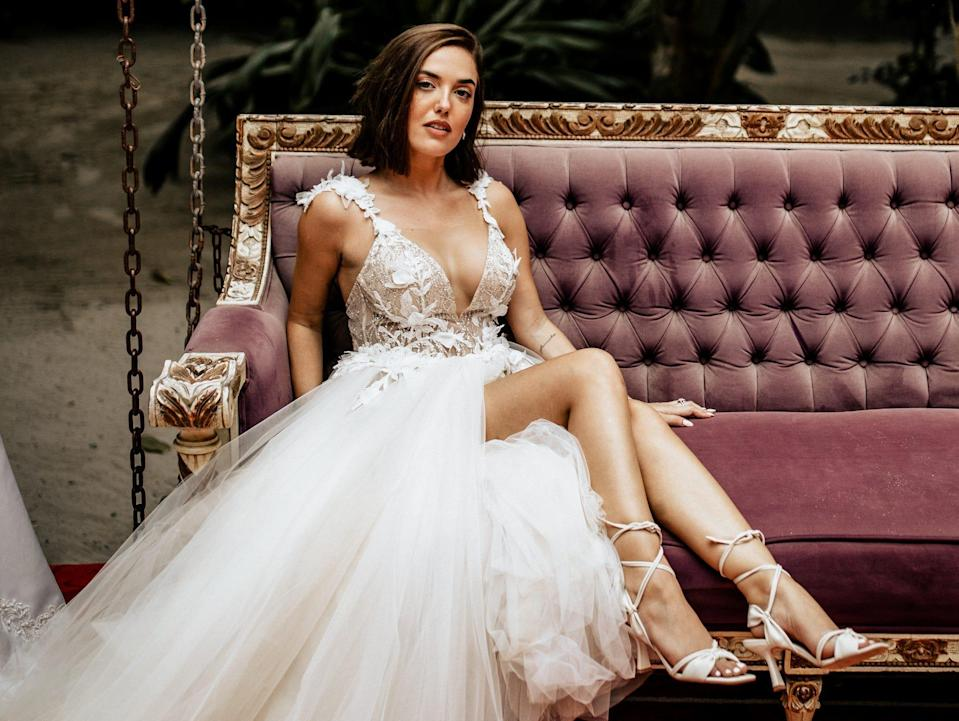 Thaina Bak poses in her wedding dress on a couch