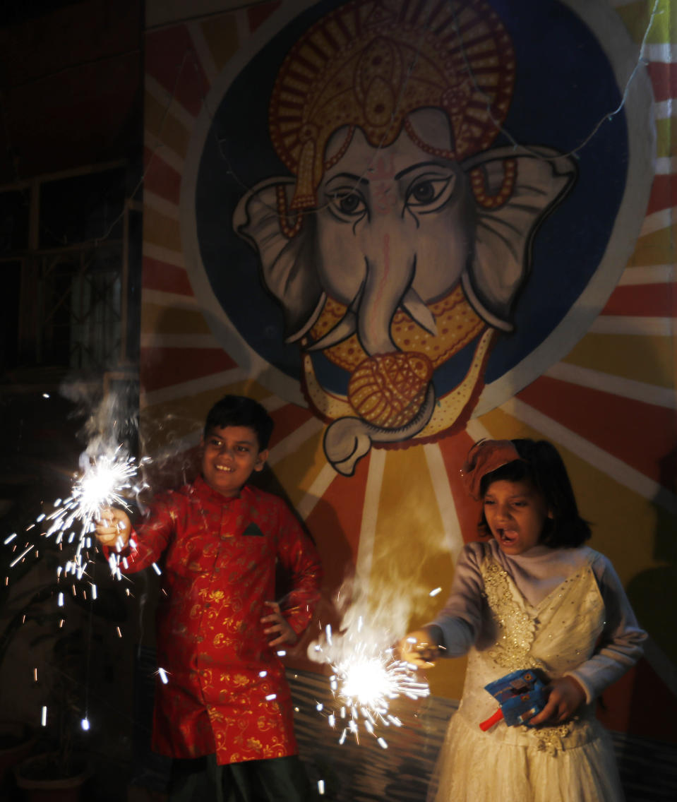 Children play with fireworks during Diwali, the Hindu festival of lights, in Prayagraj, India, Saturday, Nov. 14, 2020. Hindus across the country are celebrating Diwali where people decorate their homes with lights and burst fireworks. (AP Photo/Rajesh Kumar Singh)