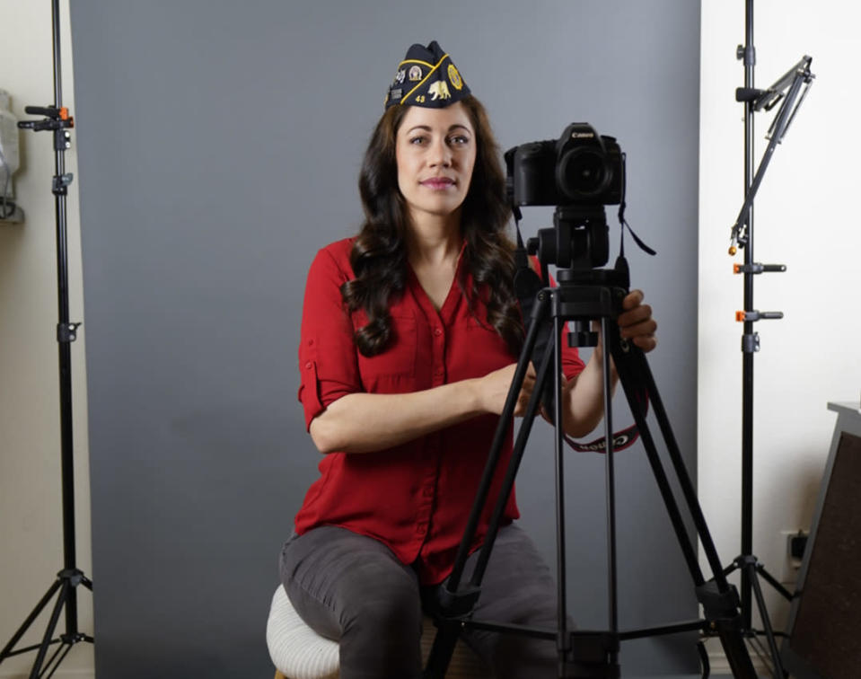 """In this June 30, 2021, Los Angeles-based producer, actress and Marine Corps veteran Jennifer Brofer poses with her blog equipment at her apartment in Los Angeles. Brofer will never forget the loud, popping noise. It was on a hot July afternoon in 2010 when her convoy rolled over an IED on a road in Helmand Province four months into her deployment to Afghanistan. Her heart froze as she and her fellow Marines stopped and realized what had occurred. But what followed were only the sounds of daily life. Brofer, 38, who now works in the film industry in Hollywood, said she feels proud to have served """"shoulder-to-shoulder with my male marine counterparts"""" in a time of war. (AP Photo/Damian Dovarganes)"""