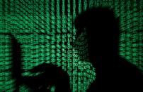 FILE PHOTO: FILE PHOTO: Man holds laptop computer as cyber code is projected on him in this illustration picture