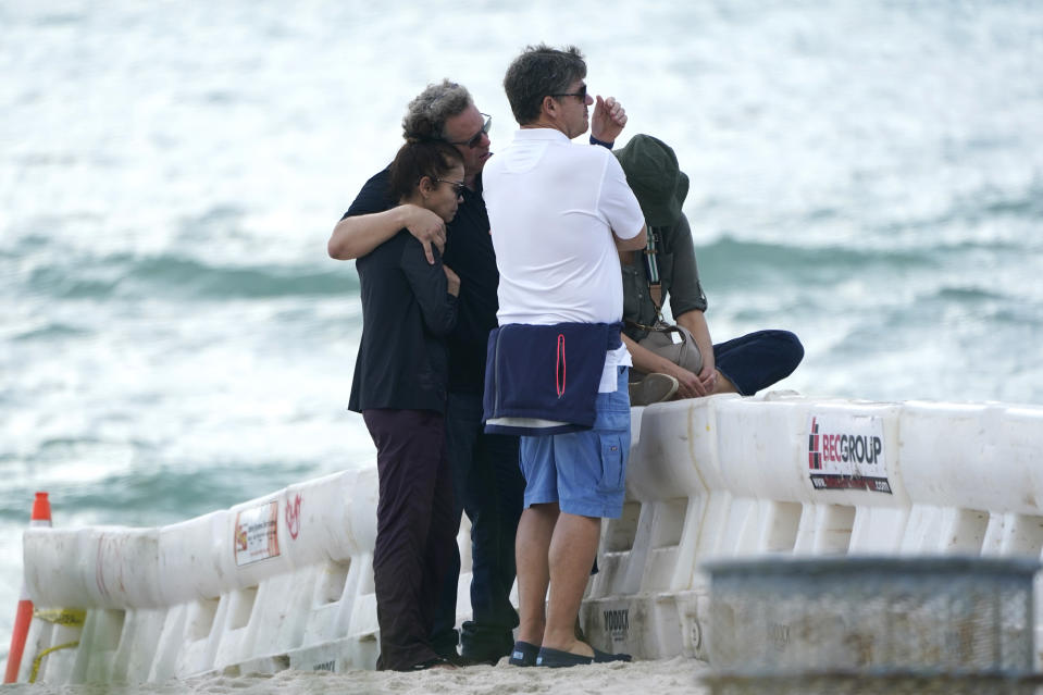 A group of people, who asked not to be identified, stand behind a barricade on the beach near the Champlain Towers South Condo building, Saturday, June 26, 2021, in the Surfside area of Miami. The apartment building partially collapsed on Thursday. (AP Photo/Lynne Sladky)