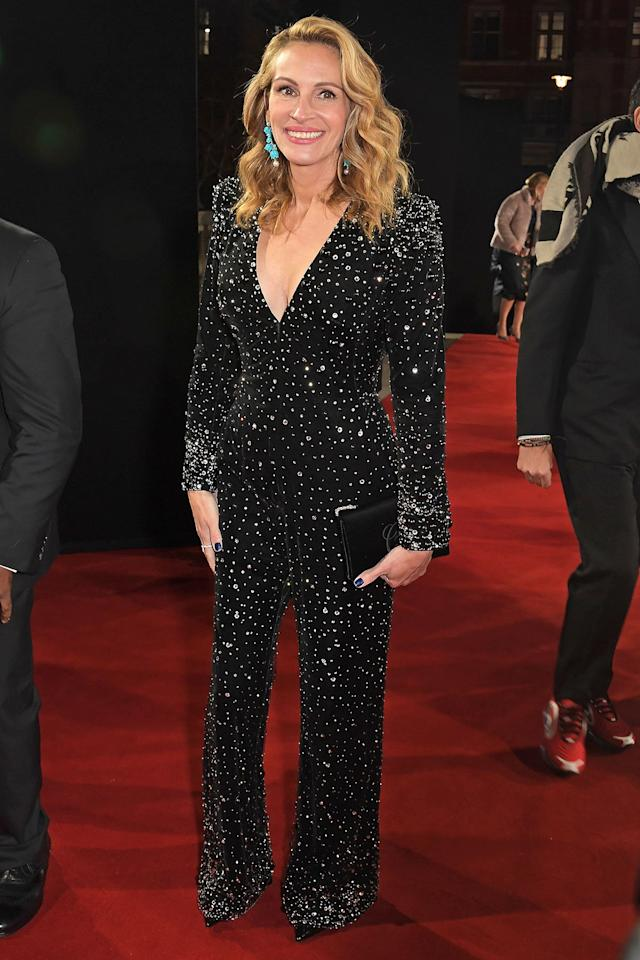 wears a plunging wide-leg Armani jumpsuit, with sequin-embellishments, long sleeves and shoulder pads.