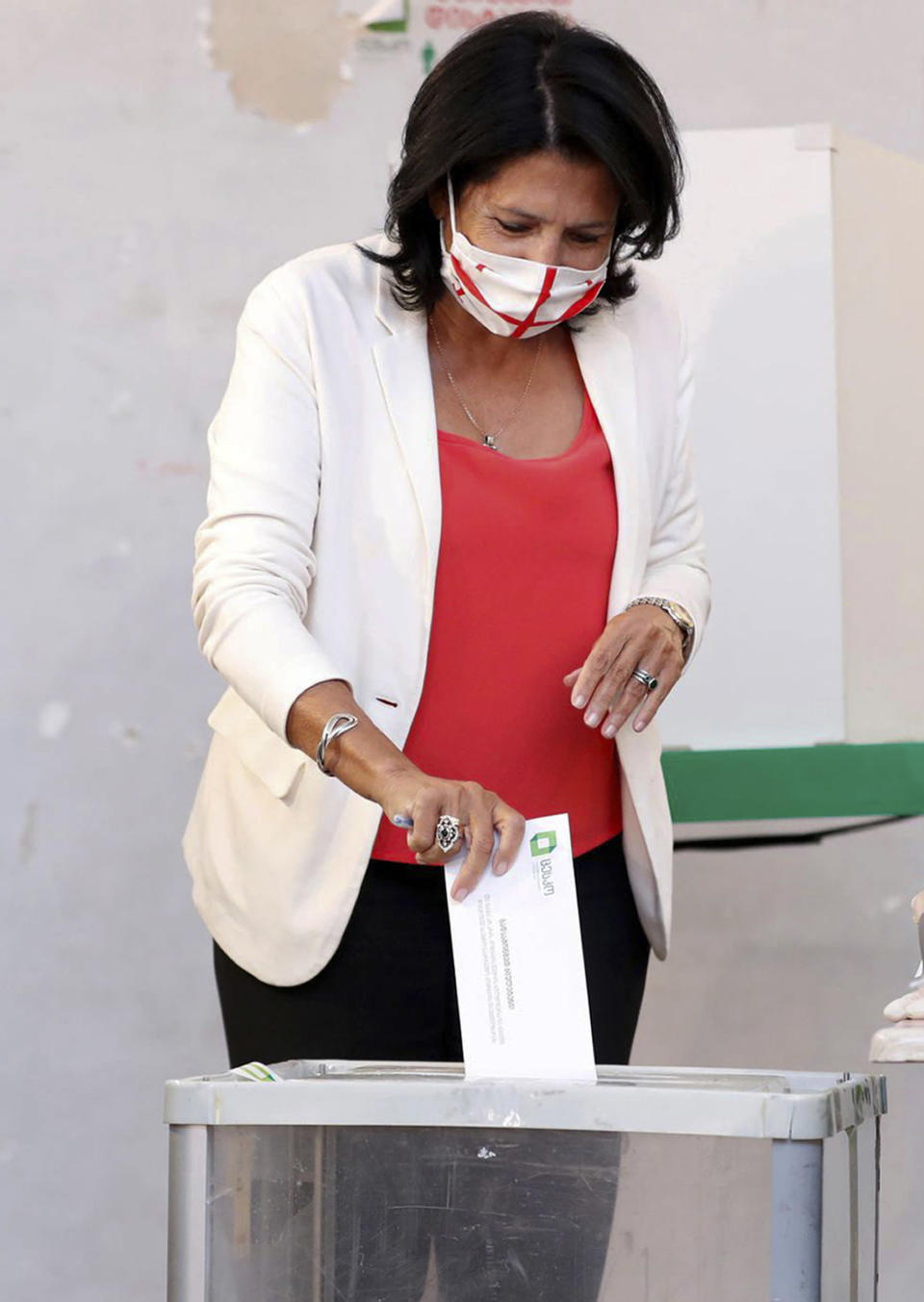 In this handout photo released by Georgia's President Press office, Georgia's President Salome Zurabishvili, wearing a face mask to help curb the spread of the coronavirus, casts her ballot at a polling station during the parliamentary elections in Tbilisi, Georgia, Saturday, Oct. 31, 2020. The hotly contested election between the Georgian Dream party, created by billionaire Bidzina Ivanishvili who made his fortune in Russia and has held a strong majority in parliament for eight years, and an alliance around the country's ex-President Mikheil Saakashvili, who is in self-imposed exile in Ukraine. (Georgia's President Press office via AP)