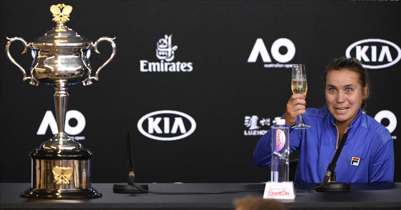 Sofia Kenin of the U.S. holds a glass of champagne during a press conference following her win over Spain's Garbine Muguruza in the women's final at the Australian Open tennis championship in Melbourne, Australia, Saturday, Feb. 1, 2020. (AP Photo/Andy Brownbill)