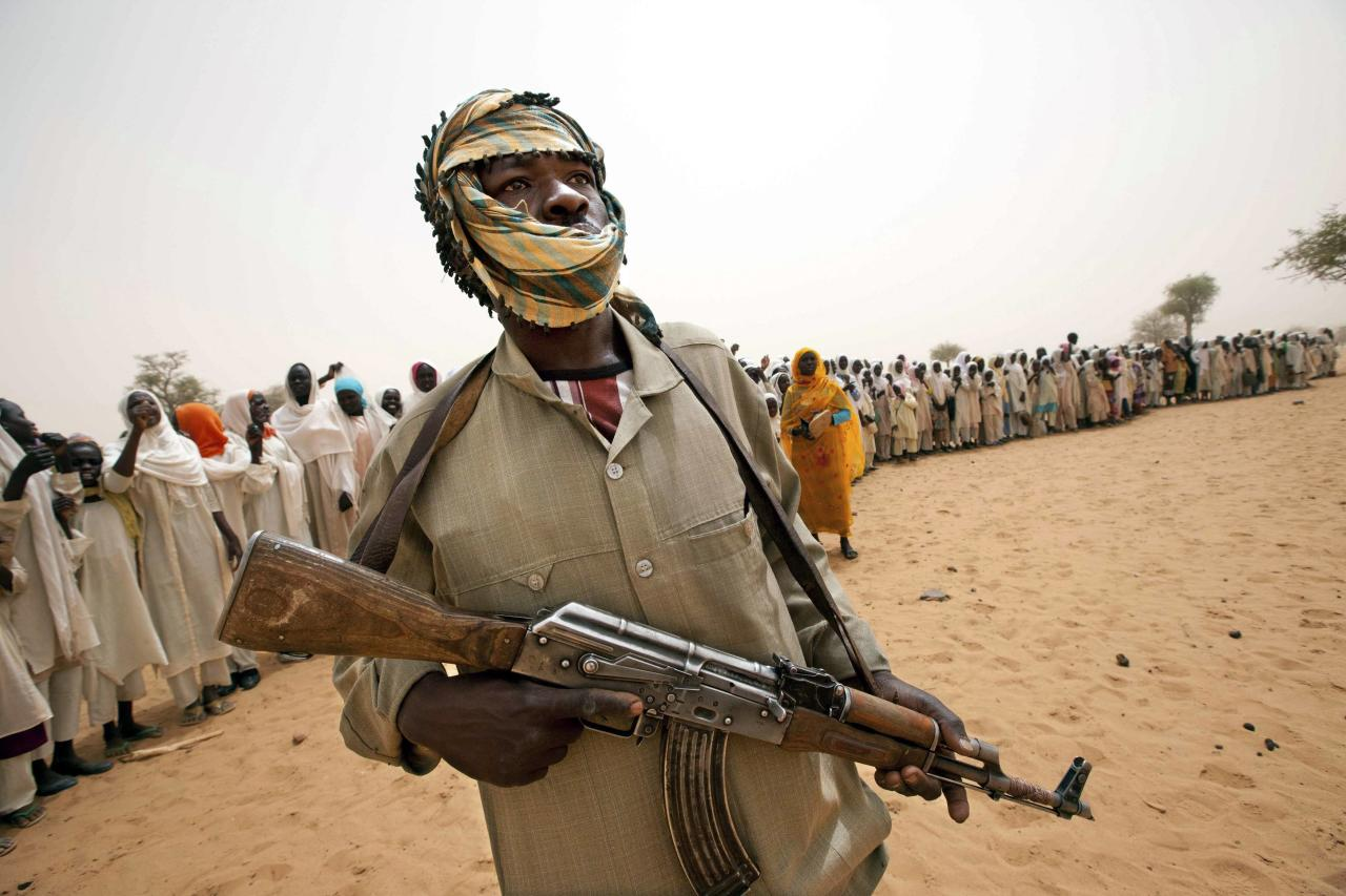 A member of the Abdul Wahid faction of the Sudan Liberation Army (SLA) rebel movement stands guard as people stand in line behind him for the arrival of an African Union-United Nations Mission in Darfur (UNAMID) delegation to open a new clinic in Forog, north Darfur in this May 30, 2012 file picture. To match Special Report SUDAN-DARFUR/GOLD REUTERS/Albert Gonzalez Farran/UNAMID/Handout via Reuters (SUDAN - Tags: MILITARY CIVIL UNREST SOCIETY BUSINESS COMMODITIES HEALTH) ATTENTION EDITORS � THIS IMAGE WAS PROVIDED BY A THIRD PARTY. FOR EDITORIAL USE ONLY. NOT FOR SALE FOR MARKETING OR ADVERTISING CAMPAIGNS. THIS PICTURE IS DISTRIBUTED EXACTLY AS RECEIVED BY REUTERS, AS A SERVICE TO CLIENTS