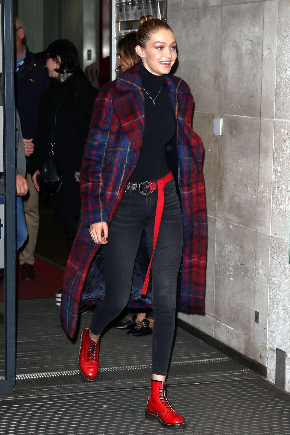<p>In a Tommy x Gigi plaid coat and skinny jeans, Wolford turtleneck bodysuit, red double-ring belt, and red patent leather Dr. Martens boots while out in London.</p>