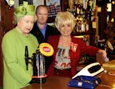 Britain's Queen Elizabeth II (L) stands behind the bar of the [Queen Victoria] pub with actress Barbara Windsor, (R) [(Peggy Mitchell)] and her on-screen son Steve McFadden [(Phil Mitchell)] during her visit to the set of BBC soap opera Eastenders in London November 28 2001 The Queen has spent a day touring various broadcasting facilities including the set of long running sopa opera Eastenders and the news room of ITN [before going on to see a rehersal of popular childrens television programme Blue Peter.]
