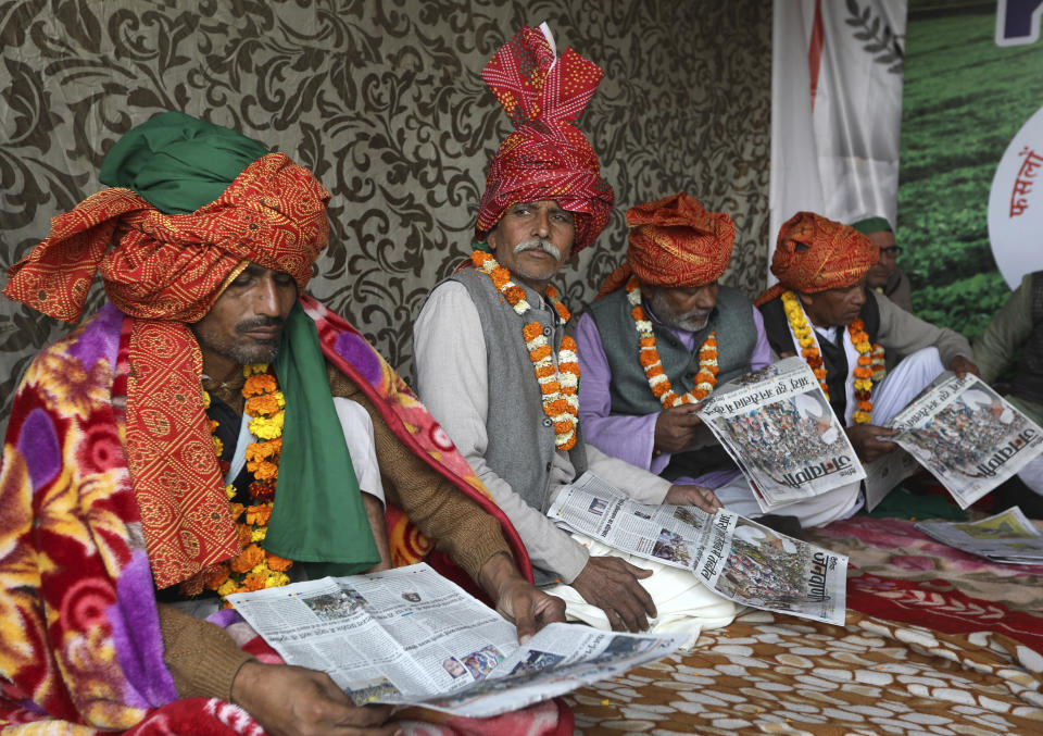 Farmers read local newspapers as they participate in a day-long hunger strike to protest against farm laws at the Delhi-Uttar Pradesh border, on the outskirts of New Delhi, India, Saturday, Jan. 30, 2021. Indian farmers and their leaders spearheading more than two months of protests against new agriculture laws began a daylong hunger strike Saturday, directing their fury toward Prime Minister Narendra Modi and his government. Farmer leaders said the hunger strike, which coincides with the death anniversary of Indian independence leader Mahatma Gandhi, would reaffirm the peaceful nature of the protests. (AP Photo/Manish Swarup)