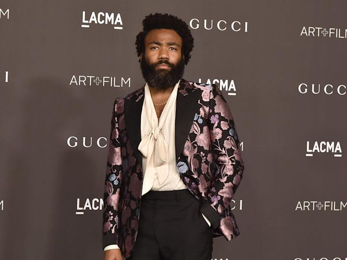 Donald Glover at an event in 2019. He wears a blazer with purple flowers over a white shirt.