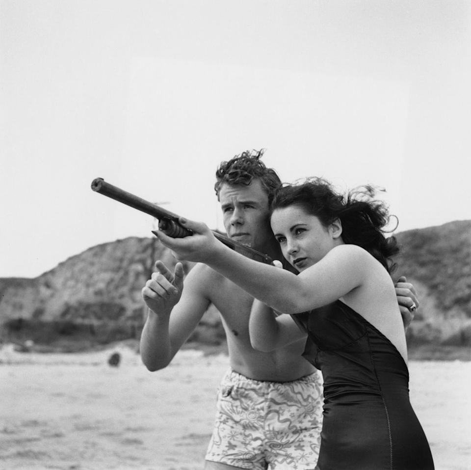 <p>Elizabeth gets a lesson from fellow actor Marshall Thompson on how to use a shot gun during a day at the beach. </p>