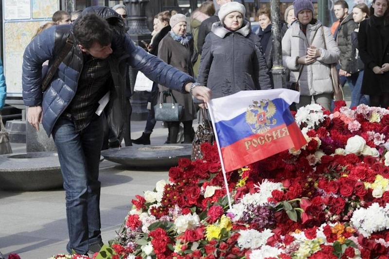 A man fixes a Russian flag at a memorial at a subway station in St Petersburg (AP)