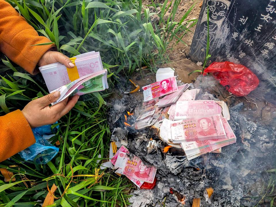 A woman burns afterlife money, a common paper sacrifice, in front of the tomb of her parents in the wheatland in Huaxian county in central China's Henan province. Photo: Getty