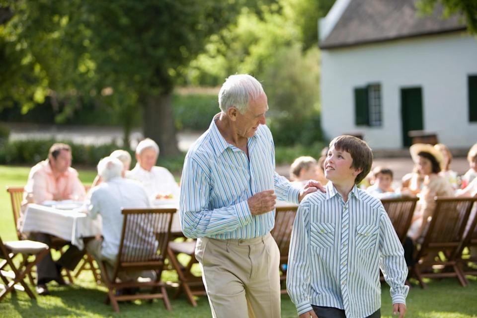 A grandfather having a conversation with his grandson at a party