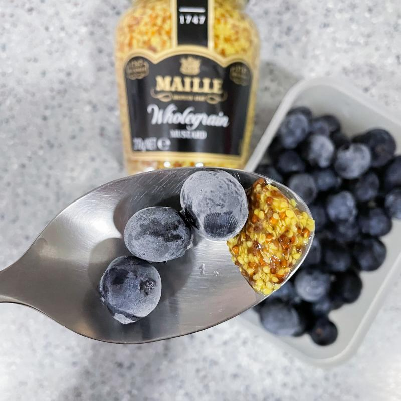 a hand in frame shot of blueberries and mustard