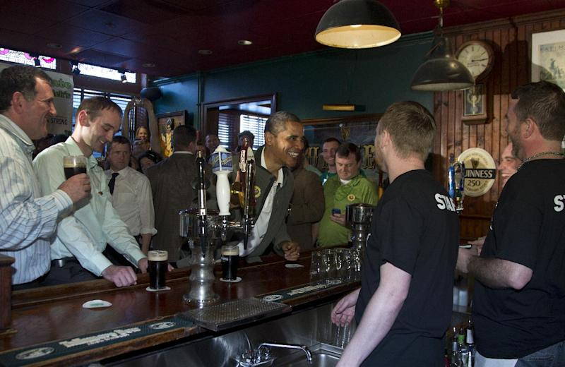 President Barack Obama talks with staff behind the bar as he drinks a Guinness with his ancestral cousin from Moneygall Ireland Henry Healy, second from left, and the owner of the pub in Moneygall Ireland, Ollie Hayes, left, at The Dubliner Restaurant and Pub and Restaurant on St. Patrick's Day, Saturday, March 17, 2012, in Washington. (AP Photo/Carolyn Kaster)