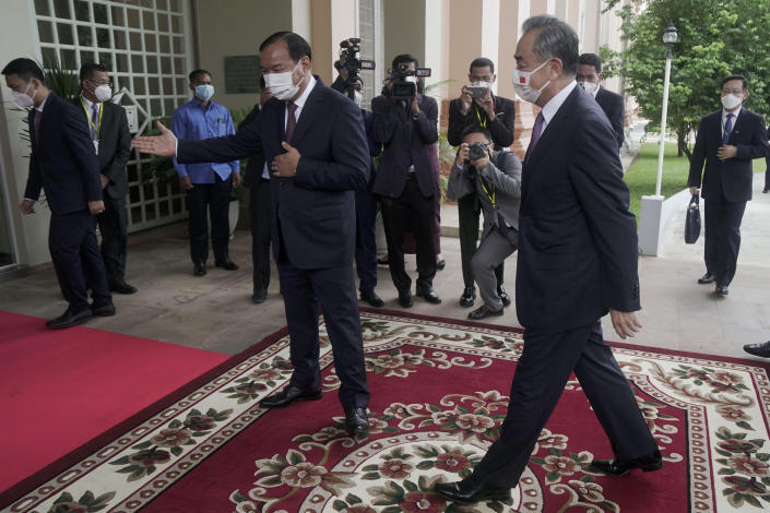 Chinese Foreign Minister Wang Yi, foreground right, is guided by his Cambodian counterpart Prak Sokhonn, center, in Phnom Penh, Cambodia, Sunday, Sept. 12, 2021. Wang is visiting Cambodia, where's he expected to meet with Prime Minister Hun Sen and other officials to discuss COVID-19 and other regional issues. (Kith Serey/Photo Photo via AP)