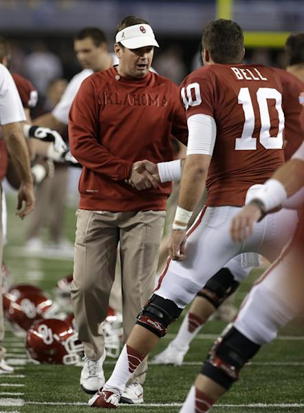 Oklahoma coach Bob Stoops shakes hands with quarterback Blake Bell (10) as the team stretches before the Cotton Bowl NCAA college football game against Texas A&M on Friday, Jan. 4, 2013, in Arlington, Texas. (AP Photo/Tony Gutierrez)