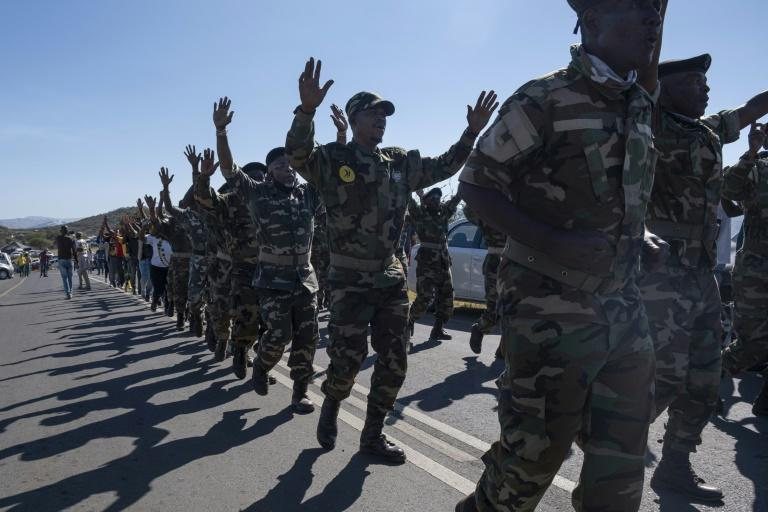 Military veterans of the anti-apartheid struggle marched on the road outside Zuma's home
