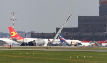 FILE PHOTO: Members of emergency services operate a crane at the scene of an incident involving an Aeroflot Sukhoi Superjet 100 passenger plane at Moscow's Sheremetyevo airport