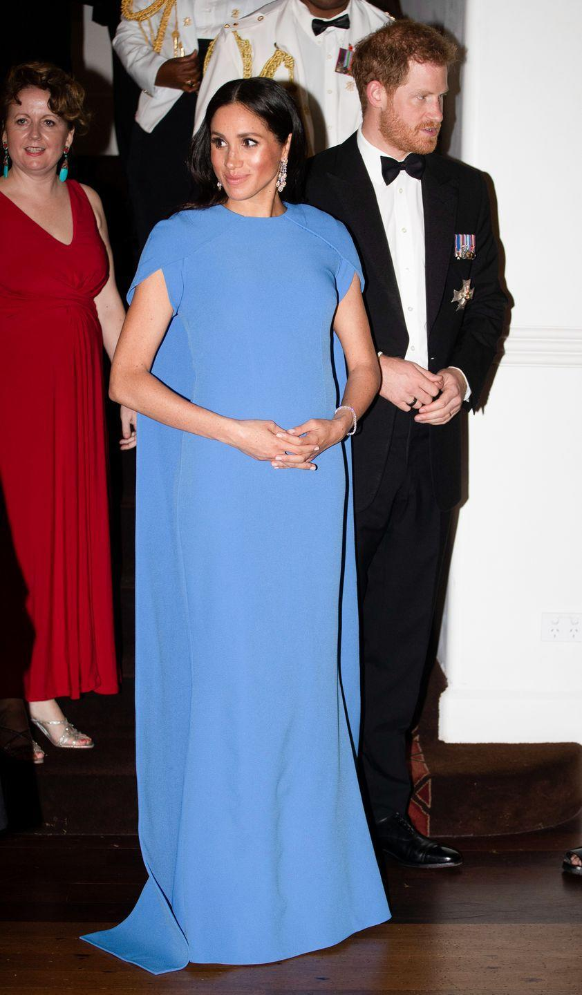 <p>Meghan Markle looked regal in a Safiyaa evening gown during her royal tour in Fiji. The cape detail reminds us of the layered skirt on Cinderella's ball gown. </p>