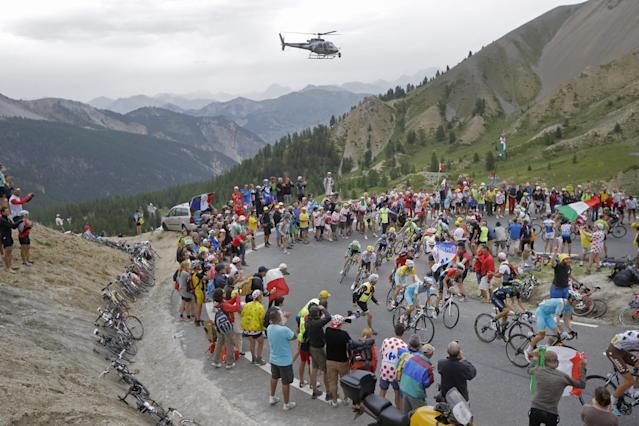 The pack with Italy's Vincenzo Nibali, wearing the overall leader's yellow jersey, climbs Izoard pass during the fourteenth stage of the Tour de France cycling race over 177 kilometers (110 miles) with start in Grenoble and finish in Risoul, France, Saturday, July 19, 2014. (AP Photo/Laurent Cipriani)