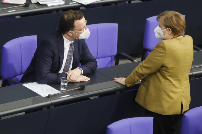 German Chancellor Angela Merkel, right, speaks with German Health Minister Jens Spahn during a debate of the German Parliament Bundestag about the coronavirus outbreak situation in Berlin, Germany, Thursday, March 4, 2021. (AP Photo/Markus Schreiber)