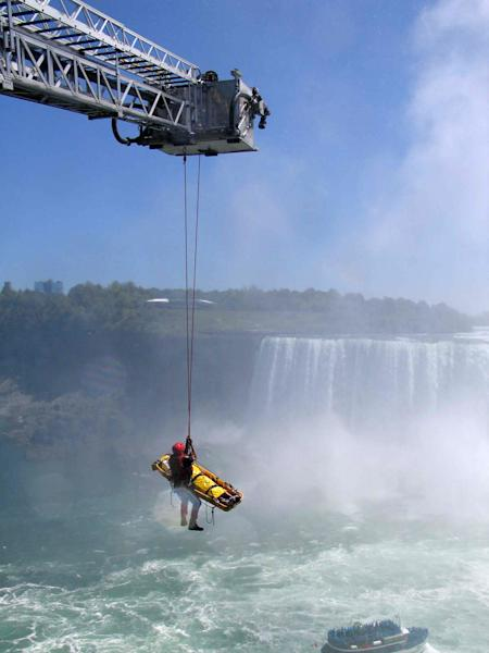 Niagara Falls emergency officials rescue a man who plunged over Niagara Falls and survived in an apparent suicide attempt, Monday, May 21, 2012. The man is only the third person known to have gone over without a safety device and live. A waiting helicopter flew him to Hamilton General Hospital, where a spokeswoman says he has critical but non-life-threatening injuries. (AP Photo/Harry Rossetani)